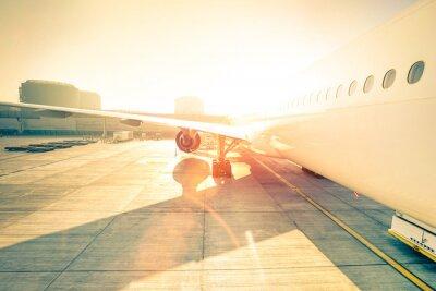 Adesivo aeroplano generico sul cancello terminale pronto per il decollo - moderno aeroporto internazionale al tramonto - Concetto di viaggio emozionale in tutto il mondo - la distorsione grandangolare con una