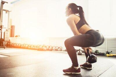 Adesivo Athletic donna che esercita con kettlebell pur essendo in posizione di squat. Donna muscolare che fa allenamento in palestra CrossFit.