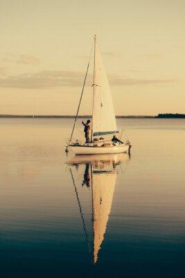 Adesivo Barca a vela su un lago calmo con la riflessione in acqua. paesaggio scena serena.