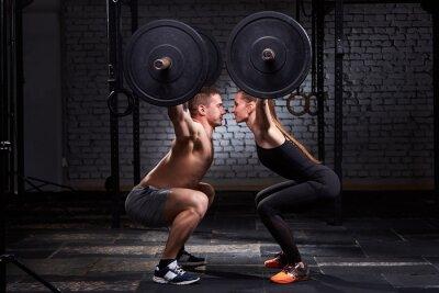 Adesivo barra di sollevamento Crossfit per uomo e donna in allenamento gruppo contro il muro di mattoni.