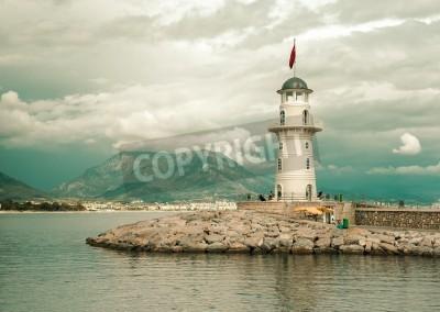 Adesivo Bellissima natura con il campo di montagne, il cielo nuvoloso e il faro nel porto di Alanya, Turchia