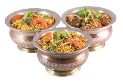 Adesivo biryani di pollo o biryani vegetariano o risotto indiano in ciotole di latta