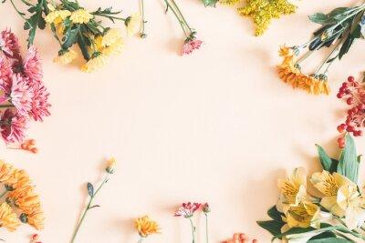 Adesivo Composizione autunnale Cornice fatta di fiori freschi su sfondo beige pastello. Autunno, concetto di caduta. Vista piana, vista dall'alto, copia spazio