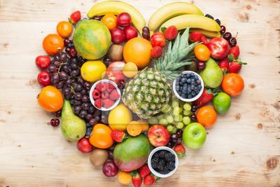 Adesivo Cuore fatto da frutti arcobaleno sani, fragole lamponi arance prugne mele kiwi uva mirtilli mango cachi ananas su tavola di legno leggera, vista dall'alto, spazio di copia, messa a fuoco selettiva