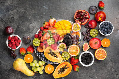 Adesivo Delicious fruit platter mango pomegranate raspberries papaya oranges passion fruits berries on oval serving plate on dark concrete background, selective focus, top view, copy space