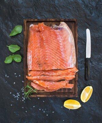 Adesivo filetto di salmone affumicato con limone, erbe aromatiche e cresciuto a bordo di legno che servono nel buio sfondo di pietra