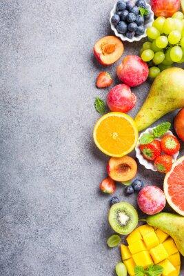 Adesivo Frutta e bacche fresche assortite su sfondo grigio chiaro. Cibo colorato pulito e salutare. Cibo disintossicante Copia spazio Vista dall'alto.