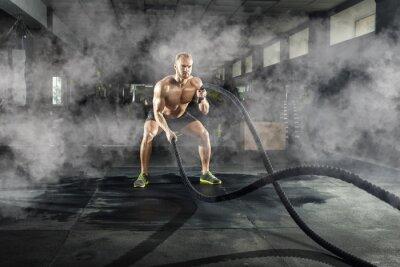 Adesivo Giovane atletico con la corda di battaglia che fa esercizio nella palestra di forma fisica. Concetto di sport.