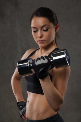 Adesivo giovane donna flessione muscoli con manubri in palestra