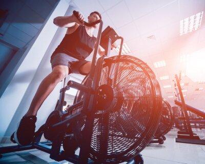 Adesivo Giovani uomini con il corpo muscoloso utilizzando air bike per allenamento cardio presso palestra di allenamento croce.
