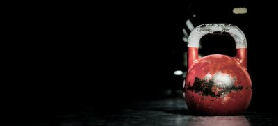 Adesivo Heavy old used color kettlebell weight on the gym floor ready for fitness strength workout to build muscles with dark background and free copy space banner