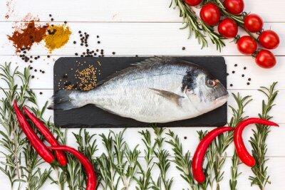 Adesivo Il pesce fresco dorado, rosmarino, pomodorini, peperoncino su bianco tavola di legno. Vista dall'alto.