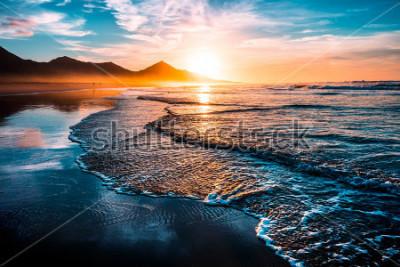 Adesivo Incredibile tramonto sulla spiaggia con orizzonte infinito e figura solitaria in lontananza e incredibili onde spumeggianti. Colline vulcaniche sullo sfondo