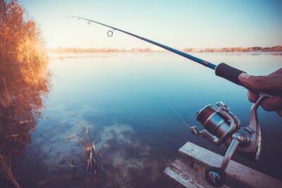 Adesivo mano con la filatura e bobina sul lago sera d'estate