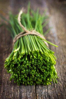 Adesivo mazzetto di erba cipollina su un tagliere di legno