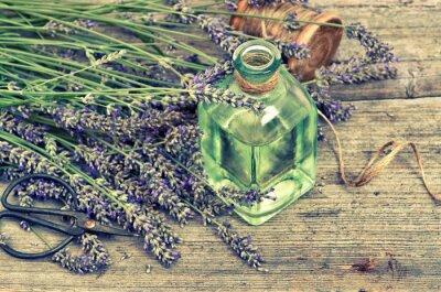 Adesivo Olio di lavanda alle erbe con fiori freschi su fondo in legno