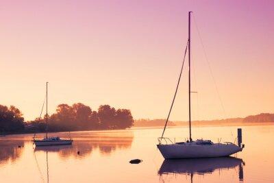 Adesivo Piccole barche a vela riflettono in acqua serena durante l'alba.