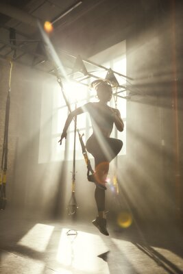 Adesivo Professional training. Full-length of young athletic woman in sports clothing training legs with trx fitness straps in the gym.