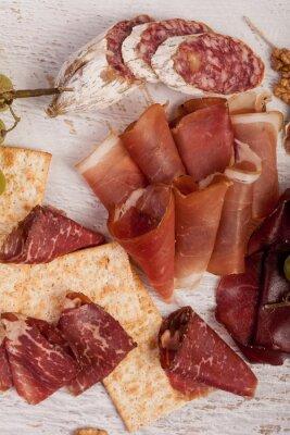 Adesivo Prosciutto, noci, cracker e uva su sfondo bianco in legno