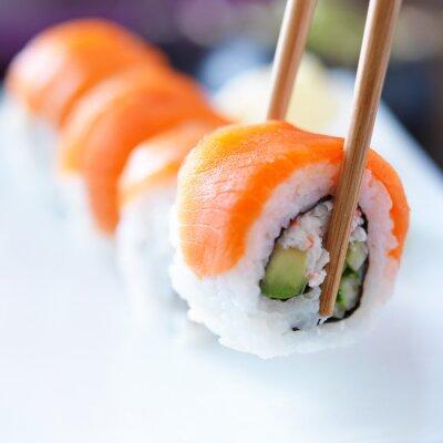 Adesivo raccogliendo un pezzo di sushi con le bacchette