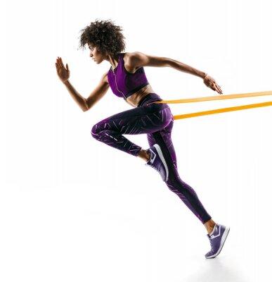 Adesivo Ragazza forte in silhouette usando una fascia di resistenza. La foto di giovane ragazza africana esegue gli esercizi di forma fisica isolati su fondo bianco. Vista laterale