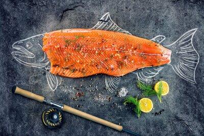 Adesivo salmone crudo di pesce bistecca con ingredienti come limone, pepe, sale marino e aneto sul bordo nero, immagine tracciato con il gesso di salmoni con bistecca e canna da pesca
