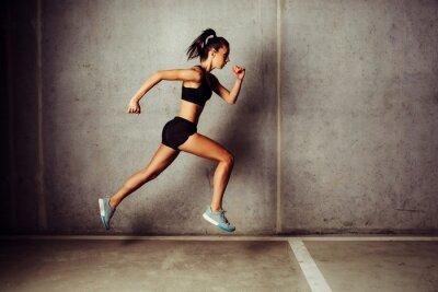Adesivo Slim attraente sportiva corsa contro un muro di cemento