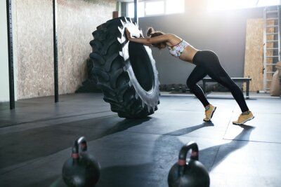Adesivo Sollevamento pesi. Addestramento della sportiva con la ruota di Crossfit alla palestra