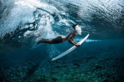 Adesivo Surfer performs dive (the duck dive) with his surfboard under the wave and exhales air into the water.