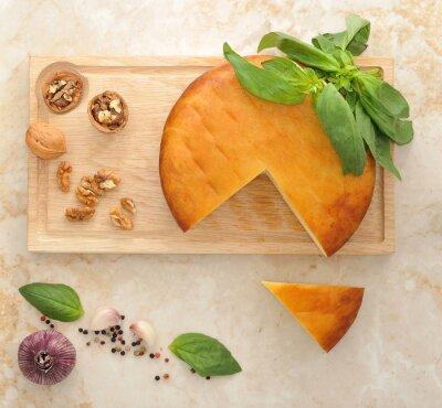 Adesivo testa di formaggio Suluguni affumicata su tavola di legno con noci e