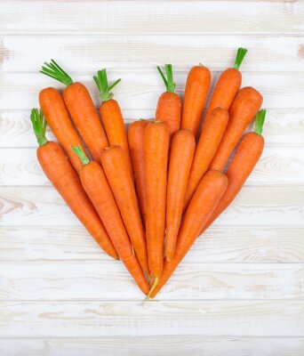Adesivo the heart of the carrot on a wood background