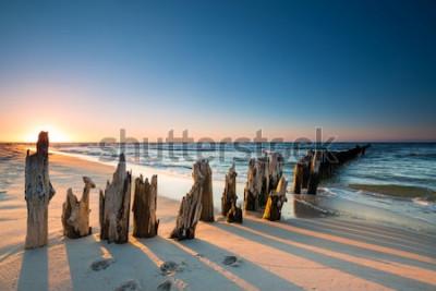 Adesivo Tramonto sulla spiaggia del Mar Baltico e sul vecchio frangiflutti in legno