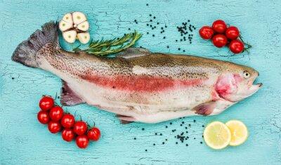 Adesivo trota pesce fresco con verdure sul tavolo in legno blu. Vista dall'alto
