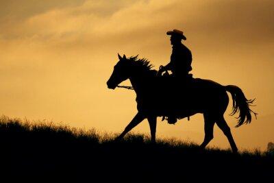 Adesivo Una silhouette di un cowboy e cavallo camminare su un prato con uno sfondo cielo arancione e giallo.