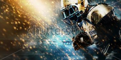 Carta da parati American football sportsman player on stadium running in action. Sport wallpaper with copyspace.