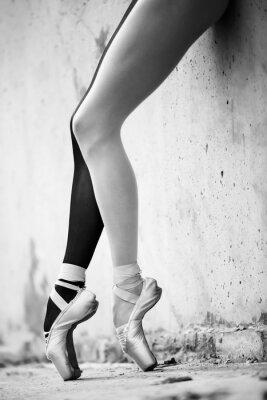 Carta da parati Ballerina feet close-up on a background of textured concrete wal
