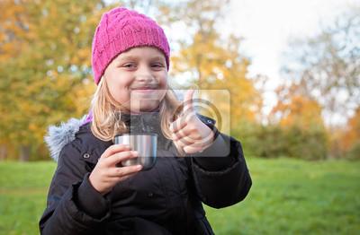 Carta da parati bambina beve il tè in parco e mostrando il pollice in alto
