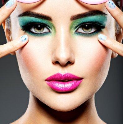 Carta da parati Beautiful Face of a woman with green vivid make-up of eyes