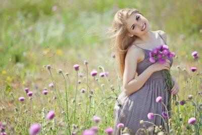 Carta da parati Bella donna con un mazzo di fiori in un campo