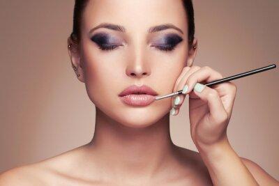 Carta da parati Bello fronte della donna. ragazza di bellezza con l'artista perfetto make-up.Makeup applica lipstick.cosmetics
