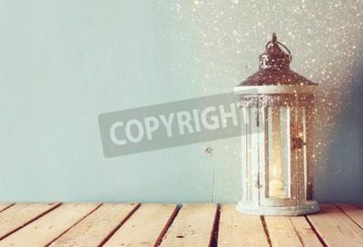 Carta da parati bianco lanterna d'epoca in legno con la masterizzazione di candela e rami di albero su tavola di legno. immagine retrò filtrata con glitter overlay