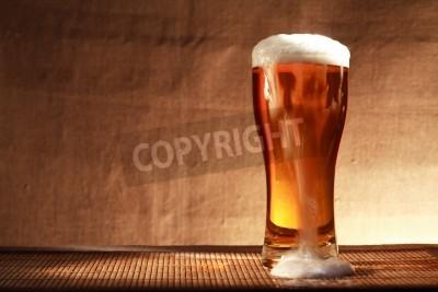 Carta da parati bicchiere pieno di birra freschezza con schiuma sul tavolo contro grigia tela di fondo