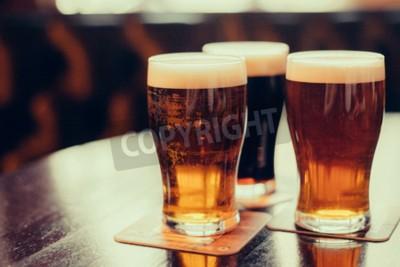 Carta da parati Bicchieri di luce e di birra scura su uno sfondo pub.