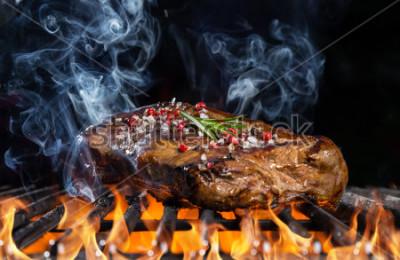 Carta da parati Bistecca di manzo sulla griglia nel fuoco con sfondo nero