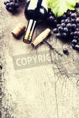 Carta da parati Bottiglia di vino rosso, uva e tappi su fondo in legno vecchio