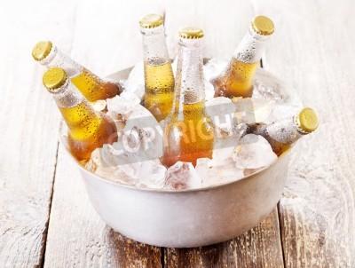 Carta da parati bottiglie di birra fredda in secchiello con ghiaccio sul tavolo di legno