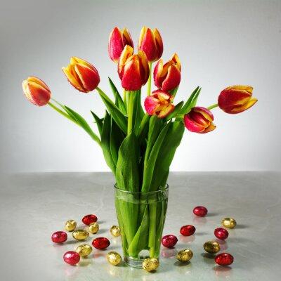 Carta da parati bouquet di tulipani freschi e piccoli cioccolato giallo rosso di Pasqua ad esempio