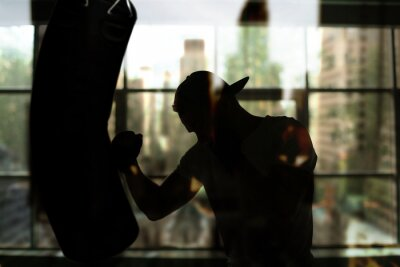 Carta da parati Boxer colpisce un sacco da boxe contro la finestra, allenamento