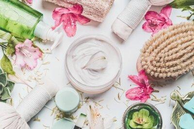 Carta da parati Crema per la pelle con petali di fiori e altri prodotti per la cura del corpo cosmetici e accessori su sfondo bianco, vista dall'alto