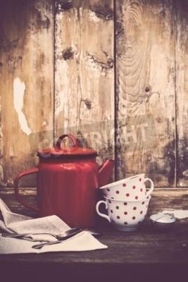 Carta da parati Decorazione di cucina vintage, piatto di caffè smalto rosso e tazze con puntini di polka su un vecchio sfondo di legno di bordo con copia spazio. Decorazione domestica rustica.